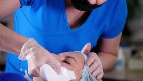Clinica di bellezza La giovane donna ottiene il massaggio facciale dal massaggiatore nella maschera con crema e lo strumento archivi video
