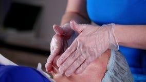 Clinica di bellezza La giovane donna ottiene il massaggio facciale professionale video d archivio