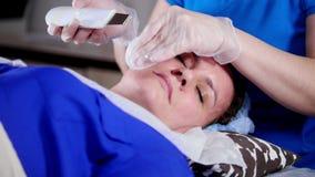 Clinica di bellezza La giovane donna ottiene il massaggio facciale professionale dal massaggiatore archivi video