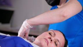 Clinica di bellezza La giovane donna ottiene il massaggio facciale professionale dal massaggiatore nella maschera stock footage