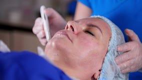 Clinica di bellezza La giovane donna ottiene il massaggio facciale relaaxing professionale dal massaggiatore nella maschera con c stock footage