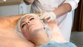 Clinica di Healtcare Il giovane cliente femminile ottiene la procedura di lifting facciale del filo Estetista in guanti che rendo video d archivio