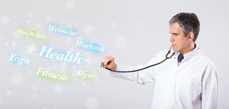 Clinical doctor pointing to health and fitness collection of words