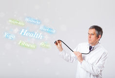 Clinical doctor pointing to health and fitness collection of wor Stock Image