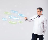 Clinical doctor pointing to health and fitness collection of wor Stock Photo