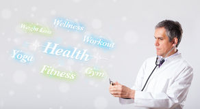 Clinical doctor pointing to health and fitness collection of wor Stock Photos