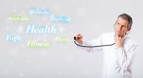 Clinical doctor pointing to health and fitness collection of wor Royalty Free Stock Images