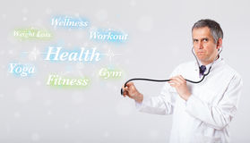 Clinical doctor pointing to health and fitness collection of wor Stock Images