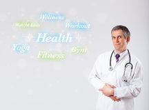 Clinical doctor pointing to health and fitness collection of wor Royalty Free Stock Photography