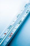Clinical thermometer. Detail of a clinical liquid-filled thermometer on a cyan blue background stock photos
