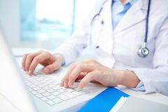 Clinician typing. Modern clinician inputting diagnosis into an online data base Royalty Free Stock Photo