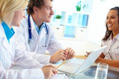 Clinicians consulting female Stock Images
