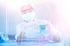 Clinicien sérieux regardant le liquide dans le flacon pendant l'examen médical Image libre de droits