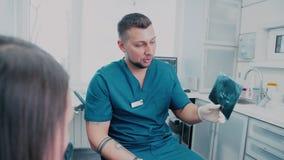 Clinique dentaire moderne L'orthodontiste dit le patient au sujet des dents clips vidéos