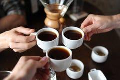 Clink стекла с 3 чашками кофе на предпосылке деталей кофе на дегустации стоковое фото
