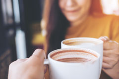 Clink coffee mugs. Close up image of man and woman clink coffee mugs in cafe royalty free stock images