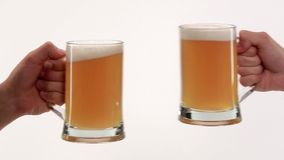 Clink glasses with beer. Two hands clink glasses with beer on white background stock footage