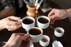 Clink glasses with three cups of coffee on the background of coffee items at the tasting Stock Photo