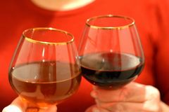 Clink wine glasses in hands holiday. Clink wine glasses in hands red background Royalty Free Stock Image