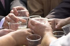 Clinked glasses. Clinked throwaway plastic glasses in a hands Royalty Free Stock Photos