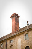 Clinker chimney on roof of ancient industrial building Stock Image