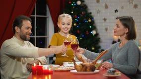 Clinking κρασί Mom και μπαμπάδων στην παραμονή Χριστουγέννων, χυμός κατανάλωσης κοριτσιών, που κοιτάζει στη κάμερα φιλμ μικρού μήκους