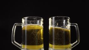 Clinking beer mugs with light golden beer in slow motion, drinking beer with friend, bubbles in beer, cheers, beer pub. Clinking beer mugs with light golden stock video footage