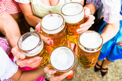 Clinking glasses with beer in Bavarian beer garden Royalty Free Stock Images