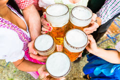 Clinking glasses with beer in Bavarian beer garden Stock Photo