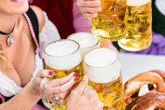 Clinking glasses with beer in Bavarian pub Royalty Free Stock Photo