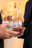 Clinking glasses with fine brandy. Royalty Free Stock Image