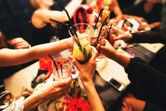Clinking glasses and toasting. Clinking glasses with alcohol and toasting, party. Congratulations to the event. Cheerful party friends royalty free stock photos