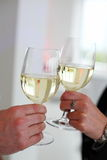 Clinking glasses of white wine glasses. Royalty Free Stock Photo