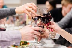 Clinking glasses of wine. Cheers after speech. Party at cafe or restaurant. Family celebration or anniversary.  royalty free stock photos