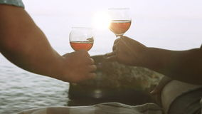 Clinking wineglasses on the wild sunny seaside Stock Images