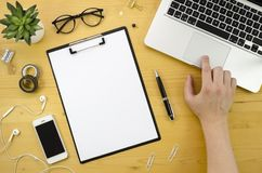 Clip board mockup with man hand and notebook, smartphone, office accessories on wood desk background. finger on the Stock Photo