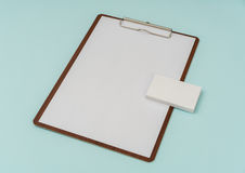 Clip board, paper and business card on blue background . Royalty Free Stock Images