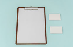 Clip board, paper and business card on blue background . Stock Images