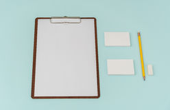 Clip board, paper,pencil  and business card on blue background . Stock Image