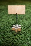 Clip card holder with wooden flower on green grass carpet holding a natural wooden announcement display with empty space for text royalty free stock photography