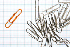 Clip de papel anaranjado con los clips de papel de plata Imágenes de archivo libres de regalías