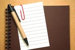 Clip de papel de nota en el cuaderno con la pluma Imagen de archivo