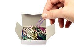 Clip de papel en una caja en un fondo blanco Imagen de archivo libre de regalías