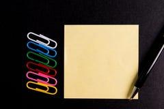 Clip de papel y nota de papel del post-it Imagen de archivo