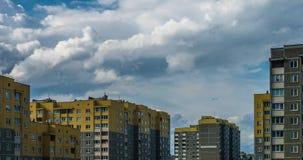Clip del lapso de tiempo de las nubes rodantes mullidas blancas contra la perspectiva de construcciones de viviendas de varios pi metrajes