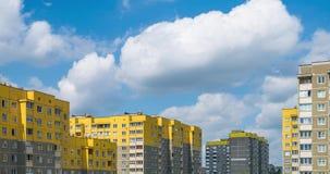 Clip del lapso de tiempo de las nubes rodantes mullidas blancas contra la perspectiva de construcciones de viviendas de varios pi almacen de video