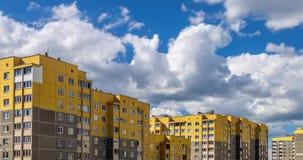 Clip del lapso de tiempo de las nubes rodantes mullidas blancas contra la perspectiva de construcciones de viviendas de varios pi almacen de metraje de vídeo