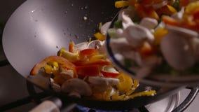 Clip del movimento lento delle verdure affettate che sono versate in un wok pronto per friggere stock footage
