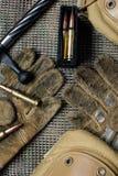 Clip della carabina, munizioni, guanti e bugie dell'otturatore su un fondo Fotografie Stock