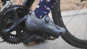 Clip della ragazza del ciclista in scarpe della strada in pedali prima dell'addestramento della corsa Chainring e fine della bici video d archivio